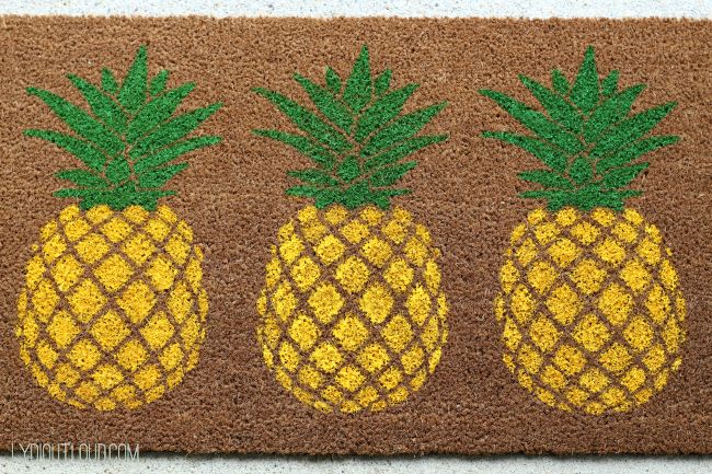 Such a fun summer DIY! This pineapple doormat was stenciled on and is a perfect addition to a summer porch.