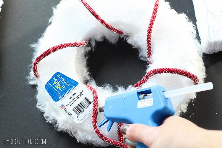 """Hot glue ribbon onto faux fur """"o""""."""